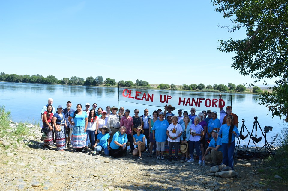 People with a sign on the shore of the Columbia River before the Hanford Journey